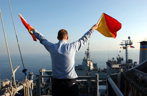 US_Navy_051129-N-0685C-007_Quartermaster_Seaman_Ryan_Ruona_signals_with_semaphore_flags_during_a_replenishment_at_sea