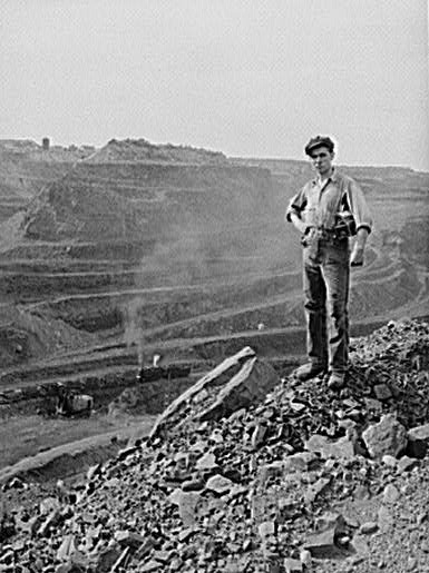 A miner poses near the edge of the pit. The pit is more than three miles (5 km) long, two miles (3 km) wide and 535 feet (163 m) deep.